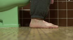 Close up of man's feet while sitting on the toilet Stock Footage