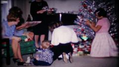 123 - presents are passed out to family at Christmas - vintage film home movie Stock Footage