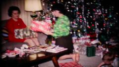107 - family and friends open gifts on Christmas - vintage film home movie - stock footage