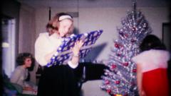 Family passes out presents on Christmas morning, 125 vintage film home movie Stock Footage