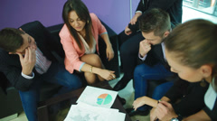 Young business people are hunched over a pie chart Stock Footage