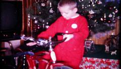 Young boy admires his new bike on Christmas, 171 vintage film home movie Stock Footage