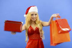 christmas woman holding gift wearing santa hat. isolated on blue background - stock photo