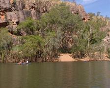 Canoeing Katherine River + tilt up sandstone escarpment, Katherine Gorge Stock Footage
