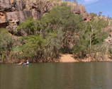 Stock Video Footage of Canoeing Katherine River + tilt up sandstone escarpment, Katherine Gorge