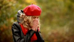 Pretty blond woman with grippe symptom in park - stock footage