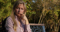 Ultra HD 4K Sad serious face blonde woman girl looking camera sitting bench park Stock Footage