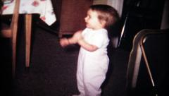 Dancing toddler entertains the family at home,139 vintage film home movie Stock Footage