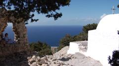Rhodes, Greece. Woman sitting in a stone window near the chapel in Monolithos. Stock Footage