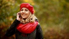 Beautiful blond woman talking on the phone in park Stock Footage