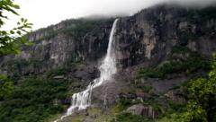 Tall waterfalls spraying its water on the rocky mountain Stock Footage