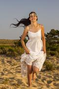 Girl with white long dress running Stock Photos