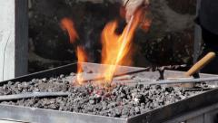 Blacksmith working on hot coal melting of an iron with fire Stock Footage