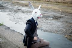 rabbit mask man in a desolate landscape - stock photo