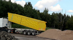 Yellow dump truck unloading soil in the site Stock Footage