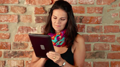 Woman using tablet and standing by the brick wall Stock Footage