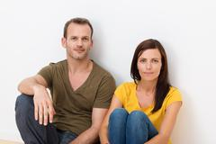 Adult couple sitting in the floor Stock Photos