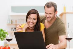 Attractive couple using a laptop in the kitchen Stock Photos
