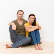 attractive young couple sitting on the floor - stock photo