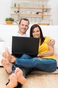 barefoot young couple relaxing with a laptop - stock photo