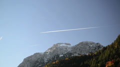 mountain top with snow in Autumn and the jetplane on blue sky - stock footage