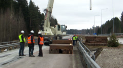 Closer view of crane carrying heavy metal beam and men working on the con Stock Footage