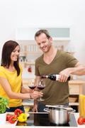 man pouring his wife a glass of wine - stock photo
