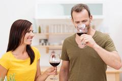 smiling couple enjoying red wine in the kitchen - stock photo