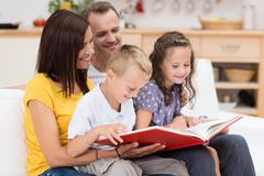 Happy family reading a book together Stock Photos