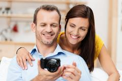 Laughing young couple looking at a photograph Stock Photos
