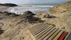 Wooden boardwalk ends on a secluded beach with rocks and lapping waves Stock Footage