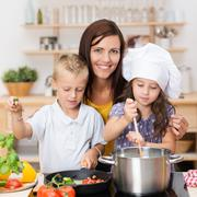 Young brother and sister learning to cook Stock Photos