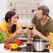 romantic couple toasting each other in the kitchen - stock photo