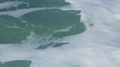 White, glistening foam on turbulant ocean, then wave breaks causing more foam Stock Footage