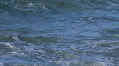 Ocean rough with sandy residue then wave breaks - stock footage