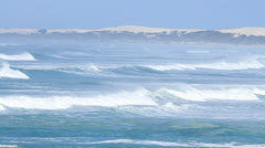 Wide shot of waves rolling past the coast with scrub and sand dunes Stock Footage