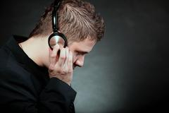young man with headphones listening to music - stock photo