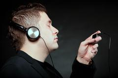 young man with headphones use mp3 music player - stock photo