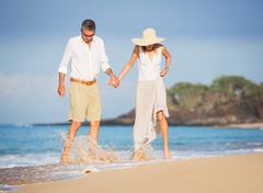 happy senior couple on the beach. retirement luxury tropical resort - stock photo