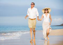 happy senior couple on the beach. retirement luxury tropical resort - stock photo