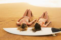 Beautiful sexy surfer girls on the beach at sunset Stock Photos