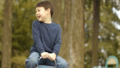 Cute Little Boy Rides Seesaw Hands Free Stock Footage