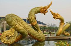 golden naga statues in the pool - stock photo