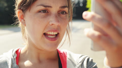Woman video messaging outdoors with mobile phone sharing Stock Footage