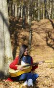 beautiful brunette guitar player girl in the forest - stock photo