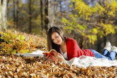 Beautiful girl with book in the autumn park Stock Photos