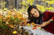 Stock Photo of beautiful girl with book in the autumn park