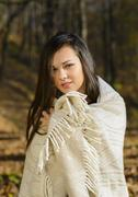 Cold woman wraps blanket over herself while standing in color autumn park Stock Photos