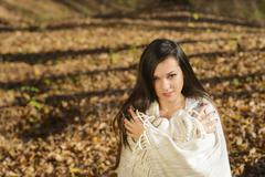 cold woman wraps blanket over herself while standing in color autumn park - stock photo