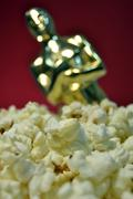 Popcorn with Oscar and red background - stock photo